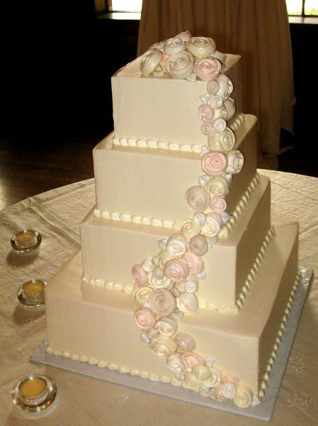 Buttercream wedding cake with piped pastel colored meringue roses