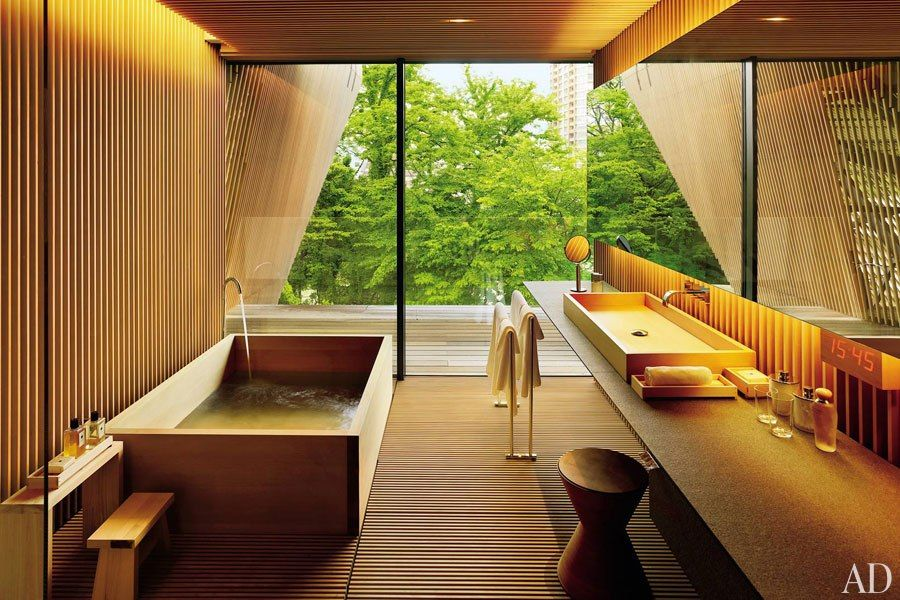 For a client in Japan, architect Kengo Kuma created a guest bath clad in wooden slats and with a striking window wall that lends the feeling of a tree house. The rectangular tub and basin are made of hiba wood and are offset by a sculptural stool. (October 2010)