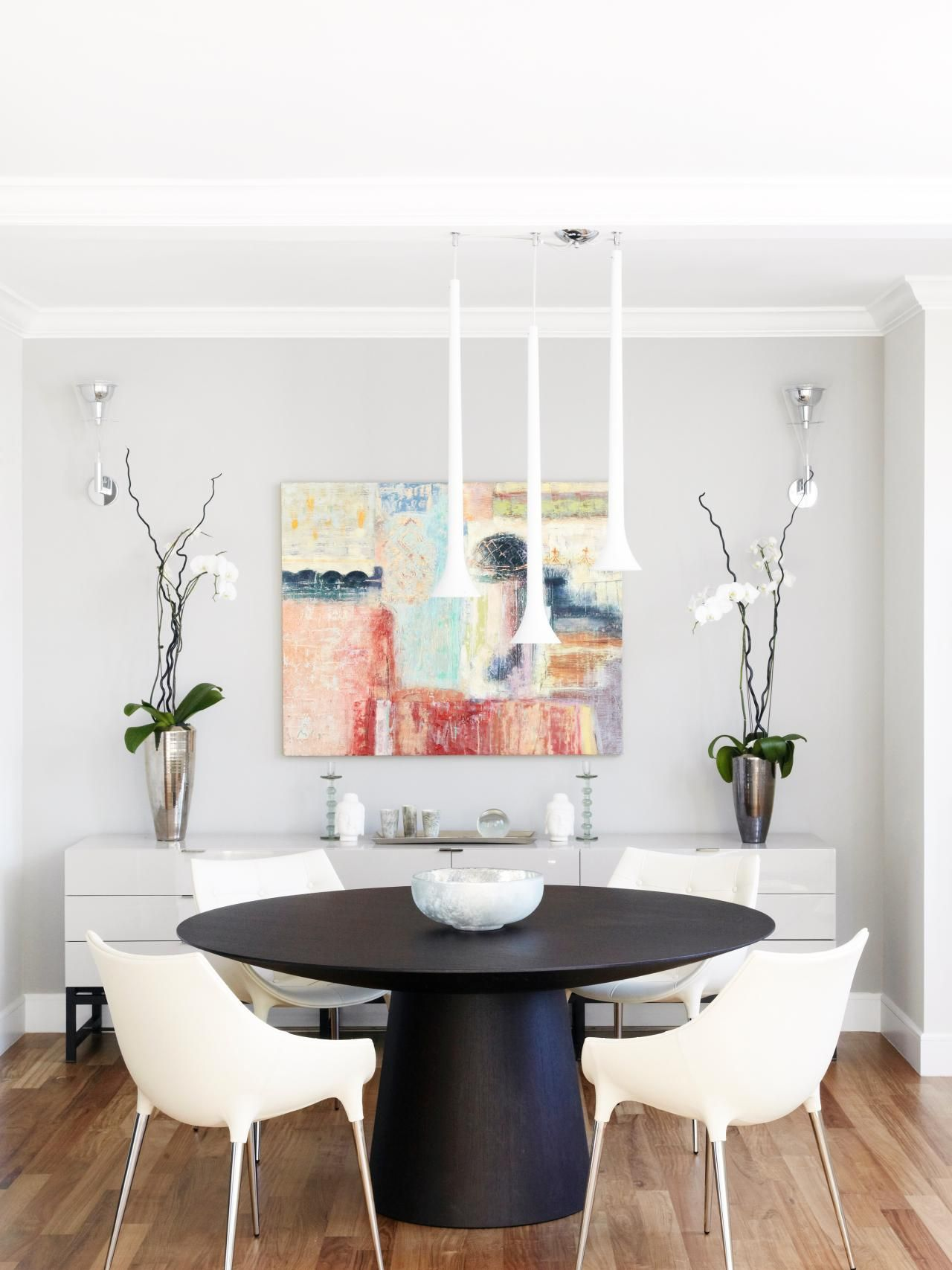 In This Modern Dining Room, Colorful Abstract Art Takes Center Stage. A  Small Black Round Table Anchors The Room While Four White Molded Plastic  Chairs ...