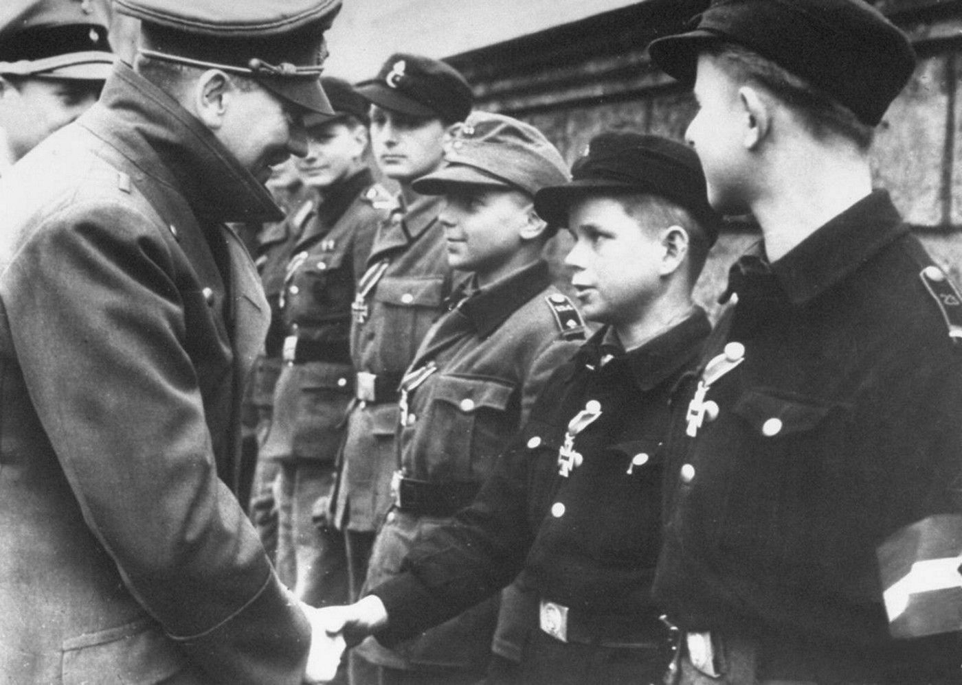 Roughly a month before he committed suicide, Hitler holds his last awards ceremony in the garden of the chancellery. The recipients are all Hitler Youth members. Hitler is shaking the hand of 12-year old Alfred Czech. To the latter's right is 16-year old Wilhelm Hubner, already a photo star thanks to receiving a medal from Goebbels as well. Both Czech and Hubner have been awarded the Iron Cross 2nd Class.