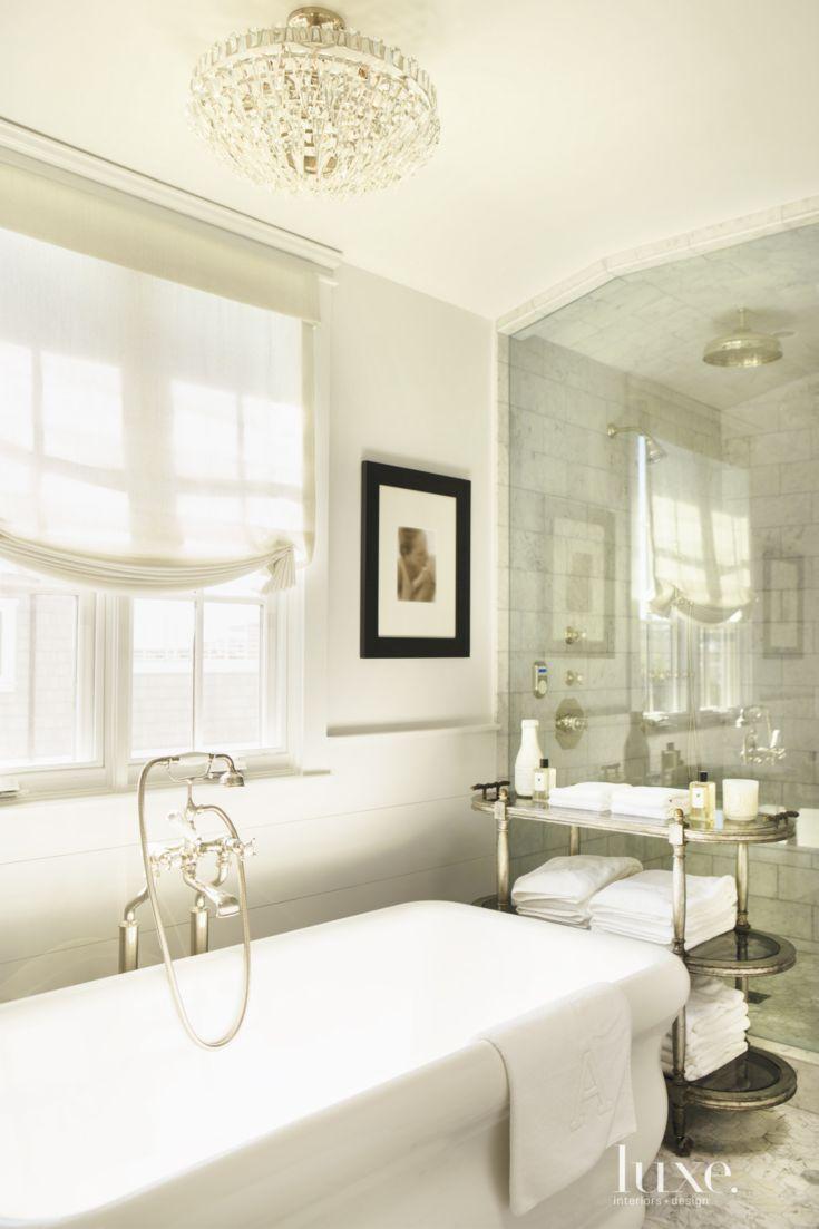 A Visual Comfort ceiling fixture illuminates the master bathroom ...