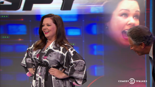 If you're like me, you're saving up all of your tears like cathartic candy for the last airing of The Daily Show this summer. But if you're like Melissa McCarthy, you've made your mourning a sartorial statement. On Wednesday, the Spy actress showed up to her Daily Show interview in a kimono made of Stewart's mug like he was the many faced god.
