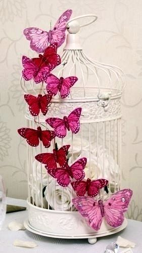 Wedding Table Decoration.. Find some vintage Bird Cages put some lovely flowers inside and affix some colorful butterflies on the outside..simple and lovely! .