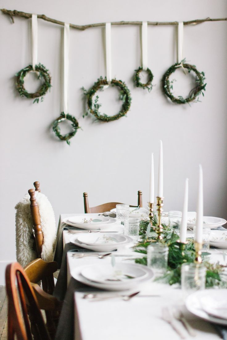 Festive dining details. Wreaths hanging from ribbon off branch against wall
