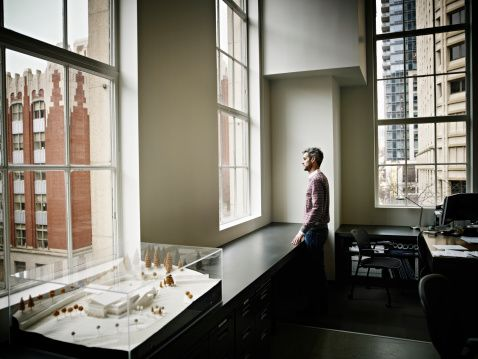 Foto de stock : Businessman looking out window at cityscape