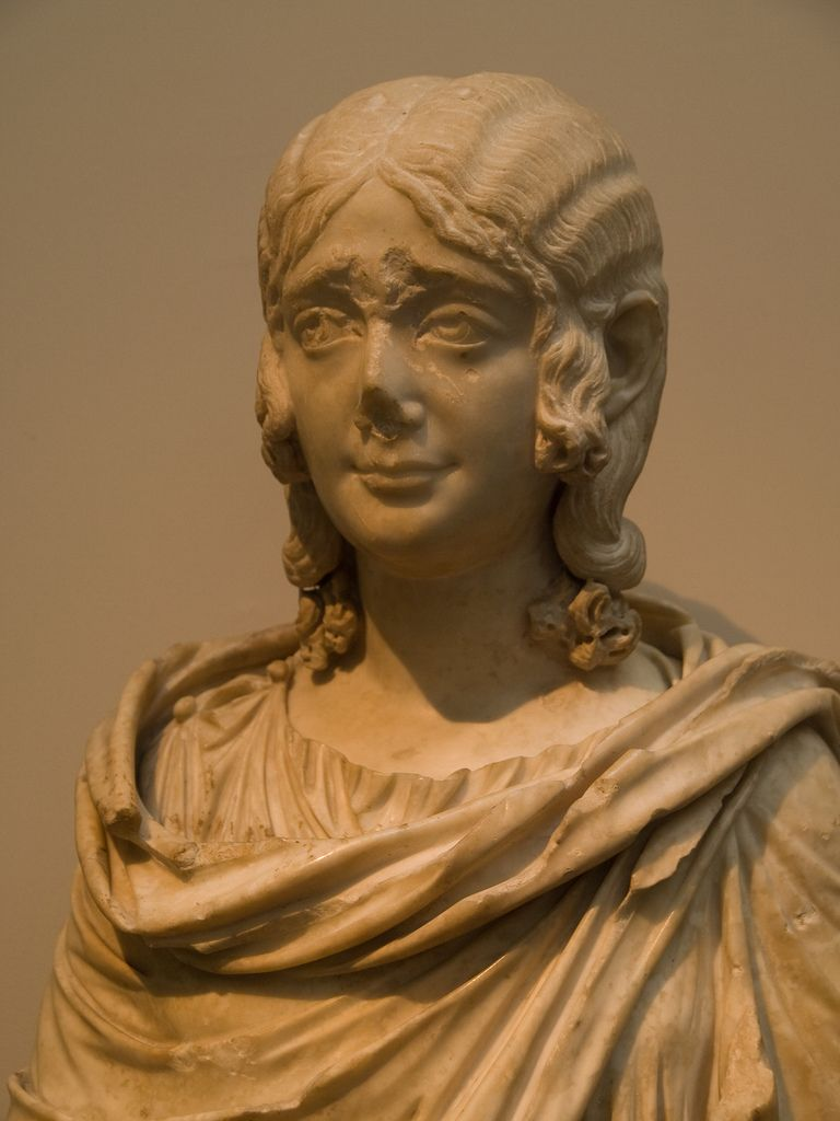 Marble portrait bust of a young girl wearing a wig  Roman, about AD 210-230   The girl wears a Greek tunic (chiton) and a cloak. The portrait reflects the contemporary fashion for extending the portrait bust to waist level.   GR 1879.7-12.13 (Sculpture 2009)