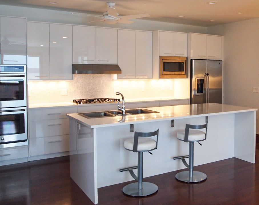 An elegant modern kitchen in all white.  Cabinets made from RAUVISIO crystal back-painted glass in high-gloss bianco.