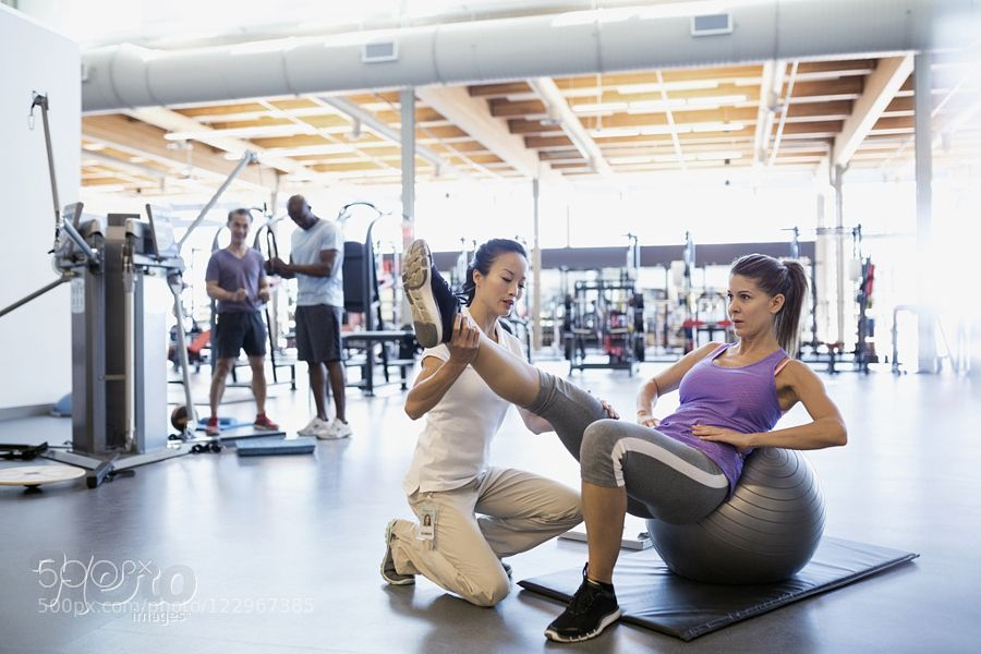 Physical therapist stretching patient leg on fitness ball