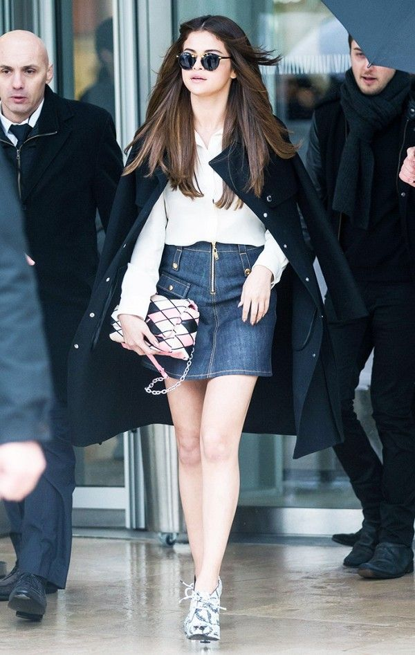 5096c5ea019 Selena Gomez wears a black coat over a white blouse with a denim skirt,  patterned bag, and printed boots