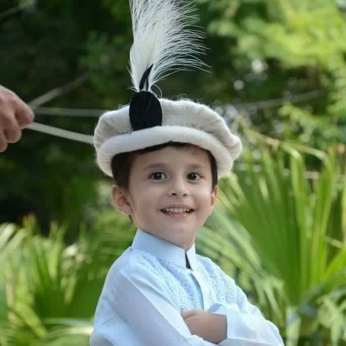 Child wearing a traditional wool Chitrali Topi (hat) with feather -  Pakistan. c36a5bf2ea5