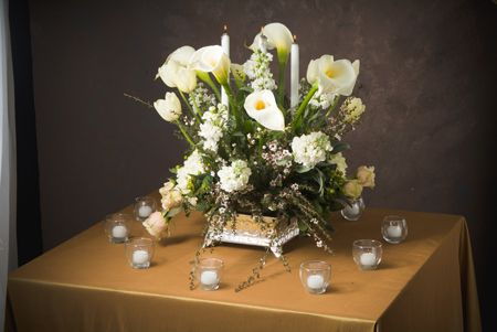 We suggest using the silver cake stand with a silver bowl filled with white hydrangea, dusty miller, white roses, sahara roses, white fresia