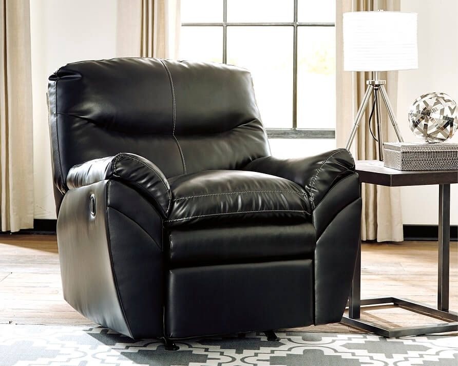 Black Faux Leather Recliner In A Room With One Window And A Side Table Next To The Chair With A Lamp On It Recliner Rocker Recliners Leather Recliner