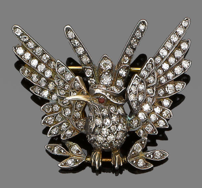 A diamond and ruby bird brooch  Realistically modelled as a bird perched on a branchwith open wings, set throughout with old brilliant and single-cut diamonds, with a circular-cut ruby eye, mounted in silver and gold, diamonds approx. 3.30cm total, French import mark, width 4.6cm