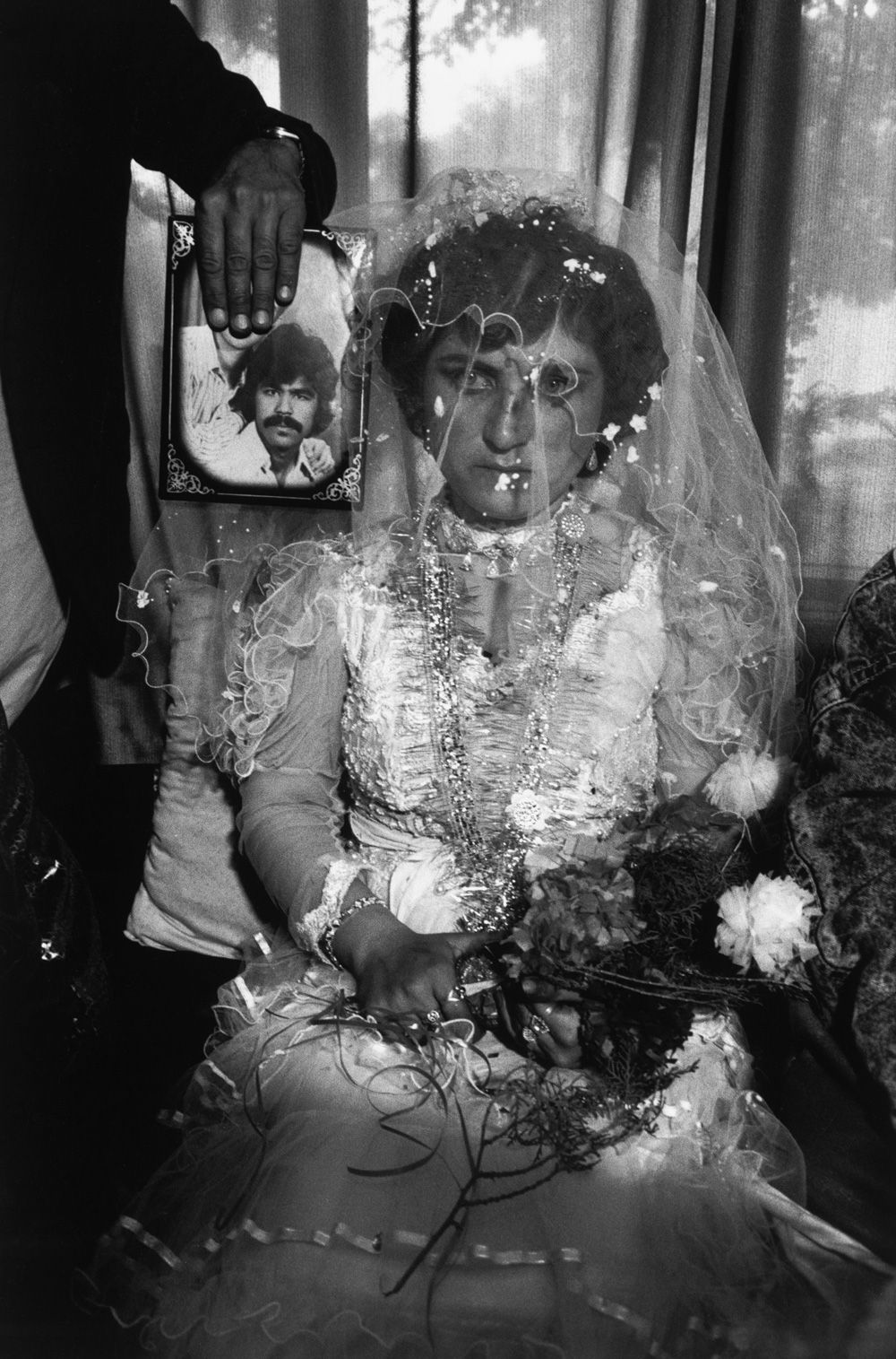 AFGHANISTAN. Kabul. A wedding by proxy- the woman's fiancé, who migrated to Germany, is present in the photograph only. 1992.