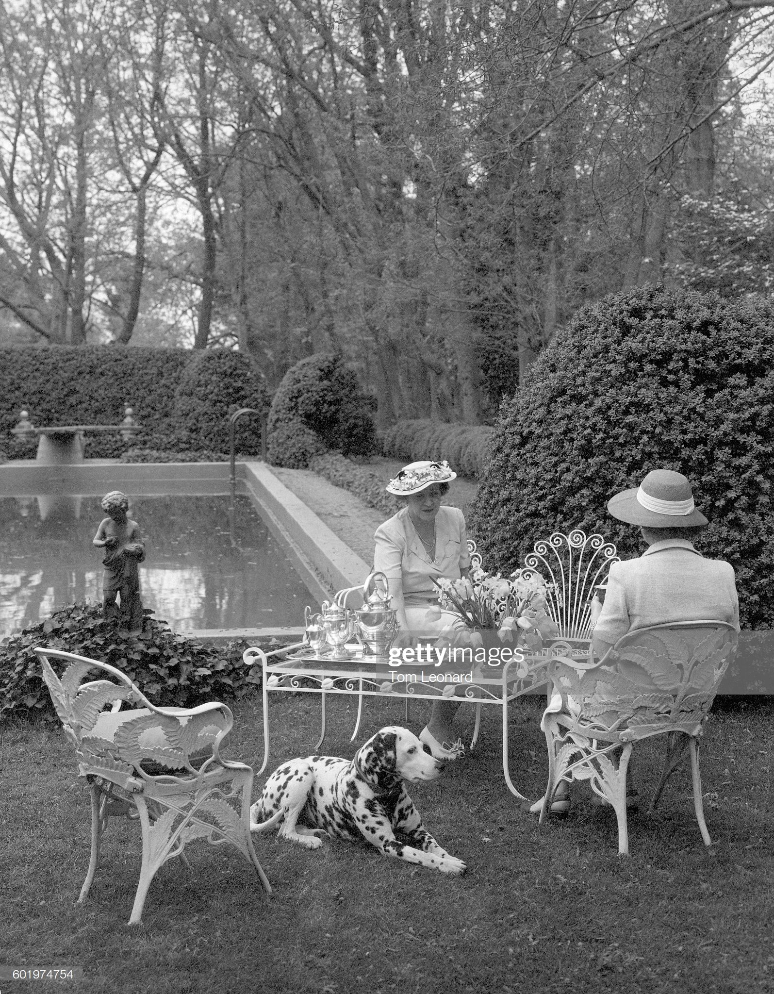 Mrs. Robert Daniel and guest have tea beside a pool, with ...