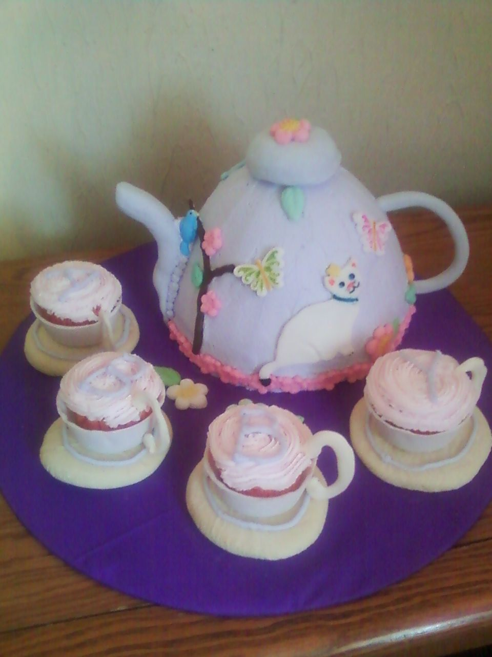 Teapot with cupcake teacups - This teapot cake was for a little girls 4th birthday. She wanted something with a kitty and her mom was doing a tea party for her birthday so this made both of them happy! Teapot was chocolate cake and tea cups were strawberry cupcakes in fondant cups, teapot frosted n BC, handle and spout were fondant/gumpaste mix. Decorations are fondant and saucers are sugar cookies.