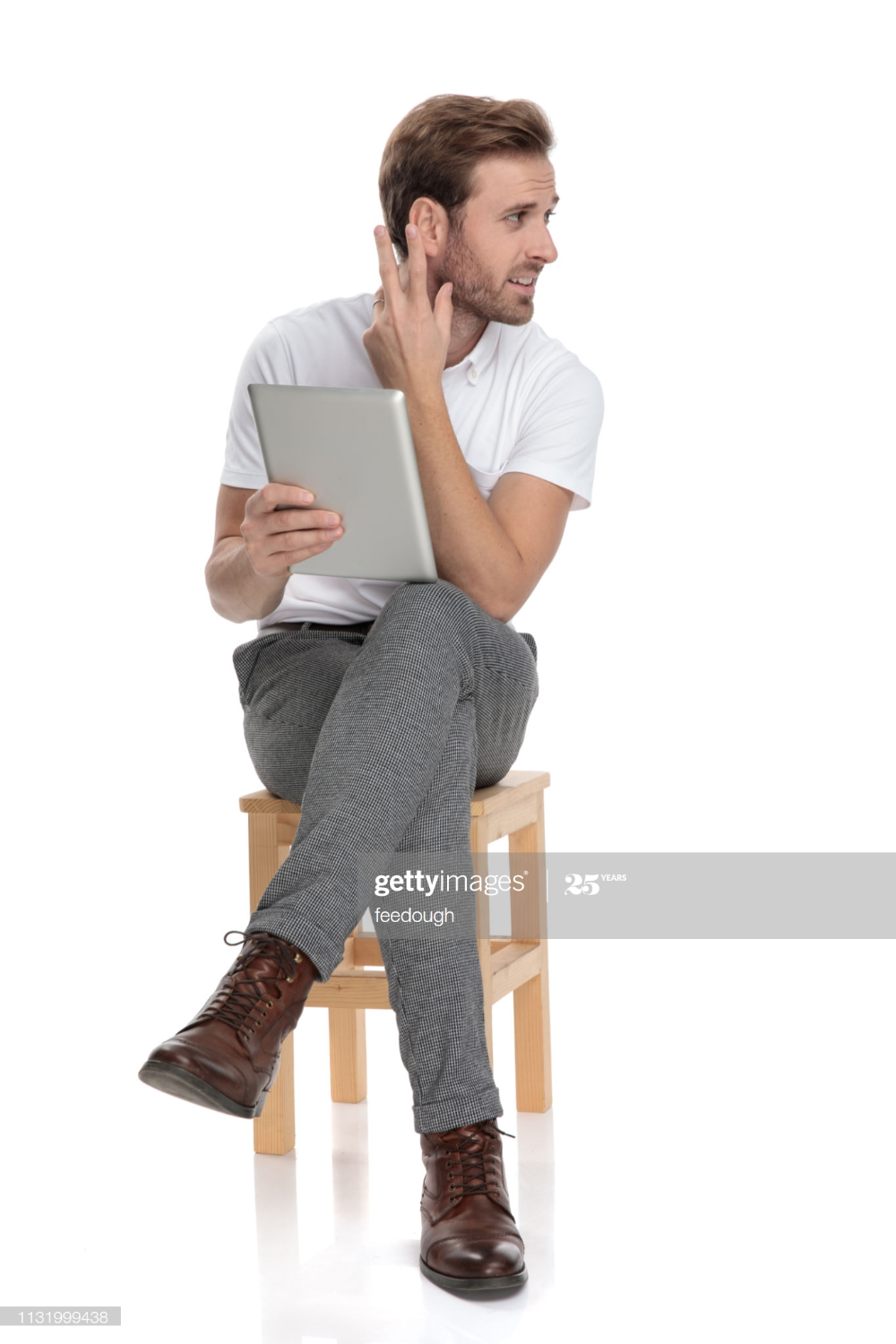 Confused And Curious Man Sitting On Chair Holds A Tablet And Gestures Man Sitting Man Curious