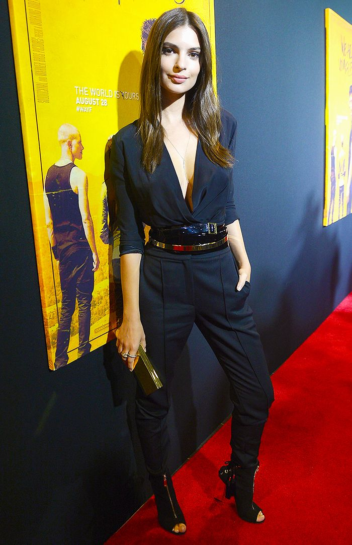 Emily Ratajkowski pairs a black belted jumpsuit with black heels, a clutch, and a silver body chain