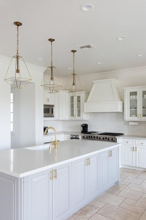 Three Gold Lanterns Hang Over A Light Gray Island Accented With - Gold kitchen pendant lights