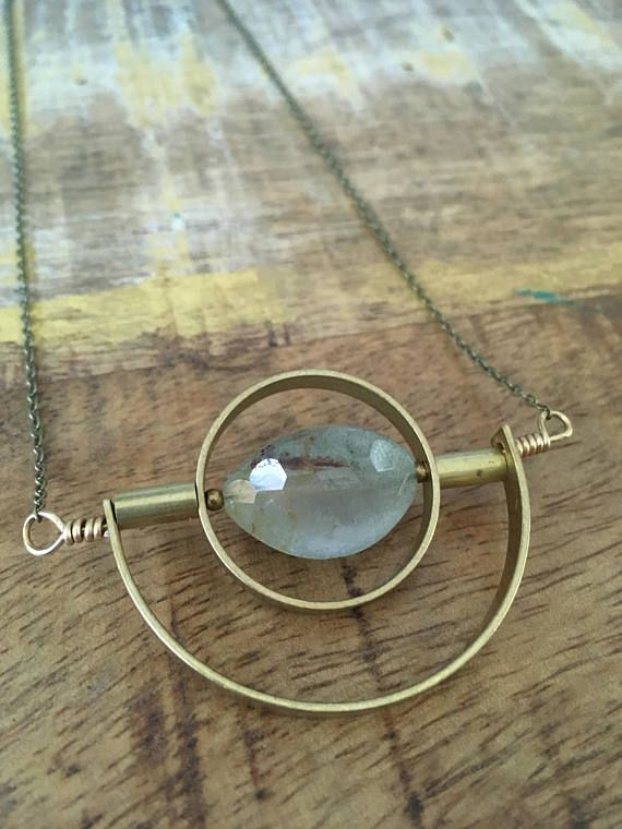 """Faceted garden quartz, brass crescent, and brass beads create a one-of-a-kind modern pendant. Brass chain with lobster claw clasp accented with tiny faceted quartz beads. Necklace measures approximately 24 1/4"""" in length."""
