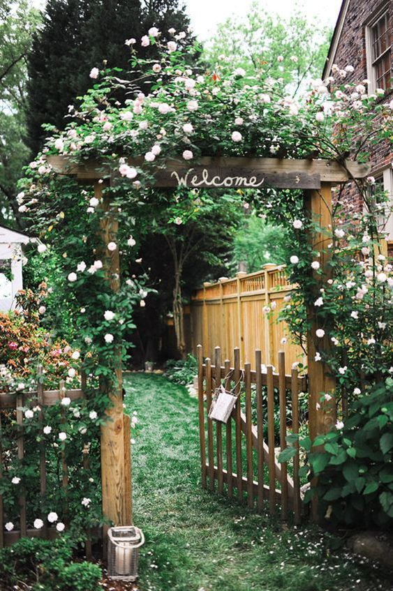 Backyard Gate This garden gate has a some what magical feel to it The roses growing over the arbor and grass path way are delightful