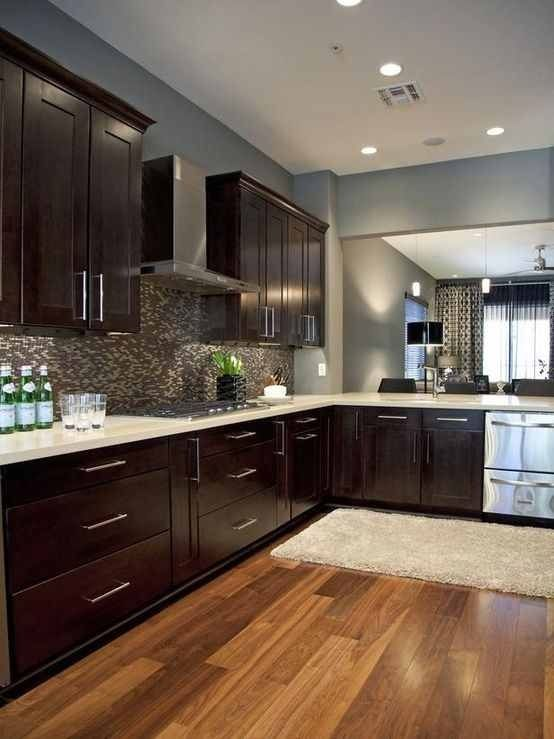 Espresso cabinets, light wood floors and light countertops ...