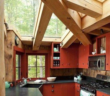 Cuisine rouge avec poutres et parquet bois dans véranda - deco maison avec poutre