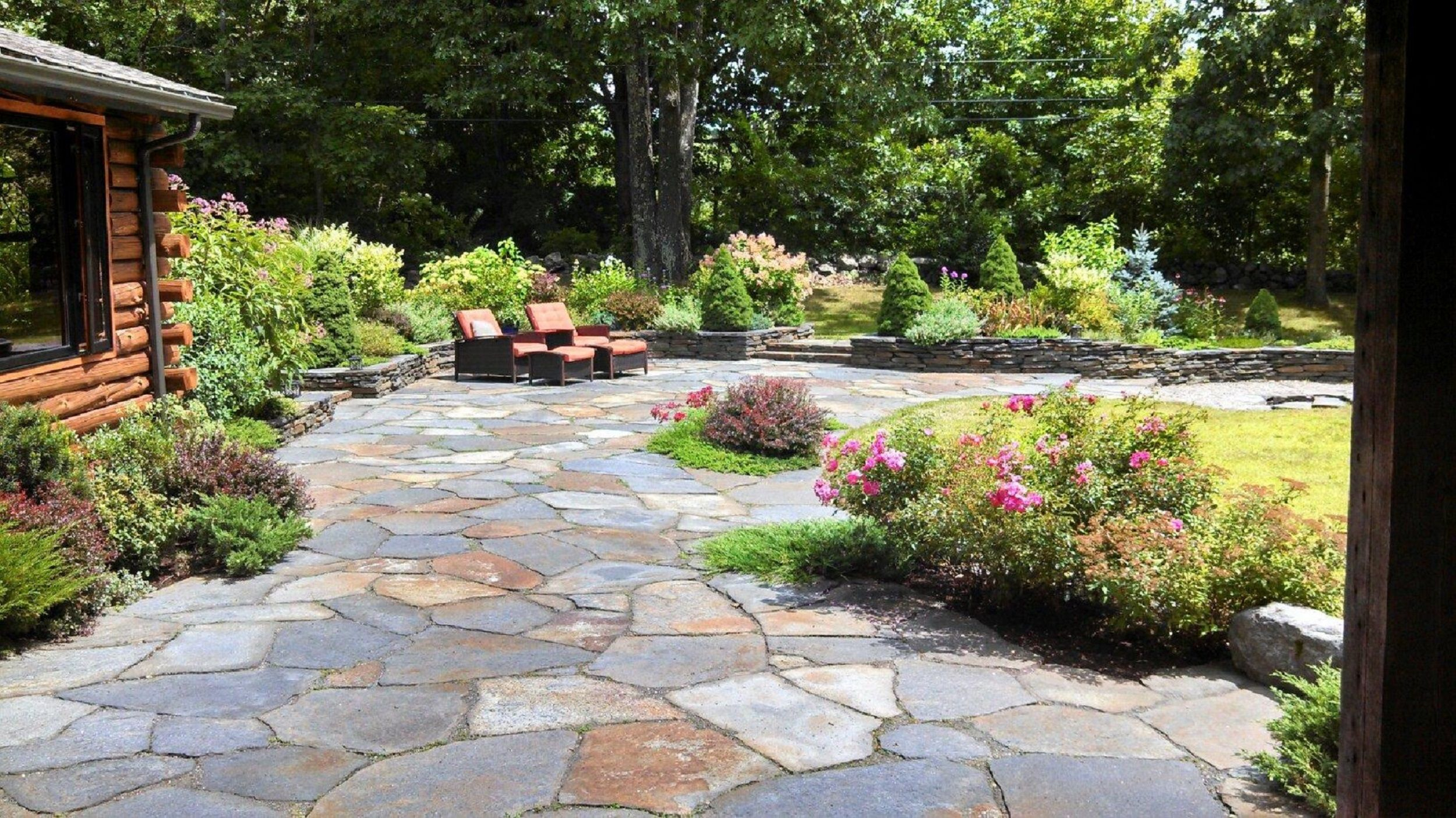 Patio and stone wall by steven breed garden designs using for Garden patio ideas