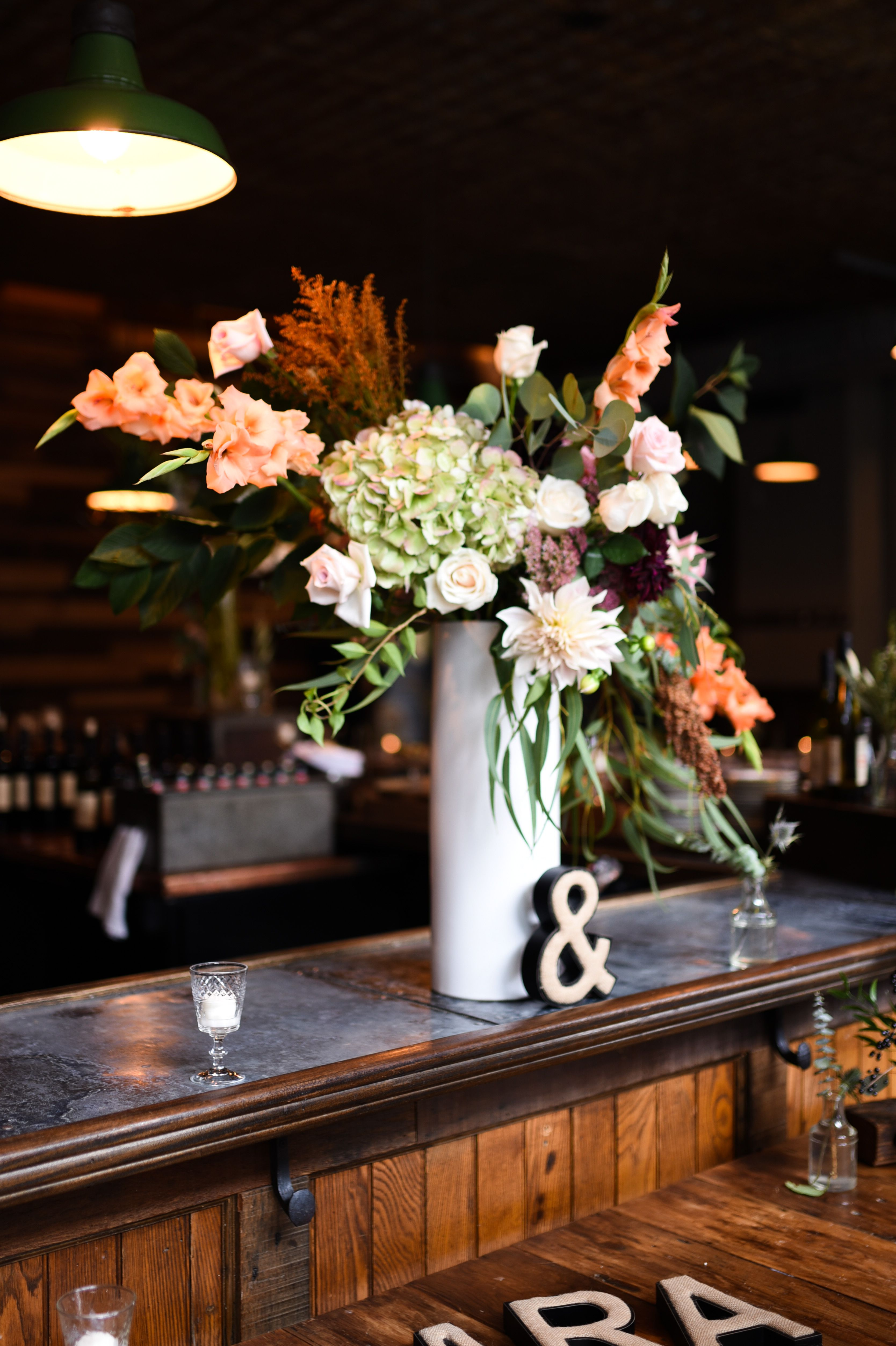 Tall asymmetrical centerpieces featuring pale flowers and