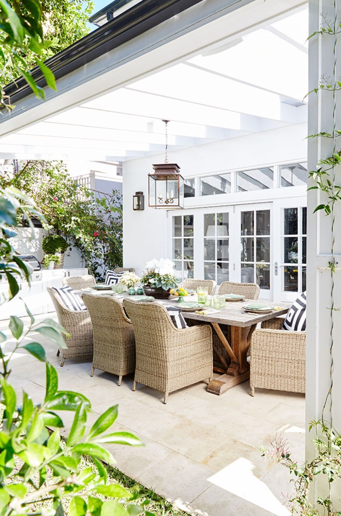 Elegant covered deck with white painted pergola, wicker chairs and ...