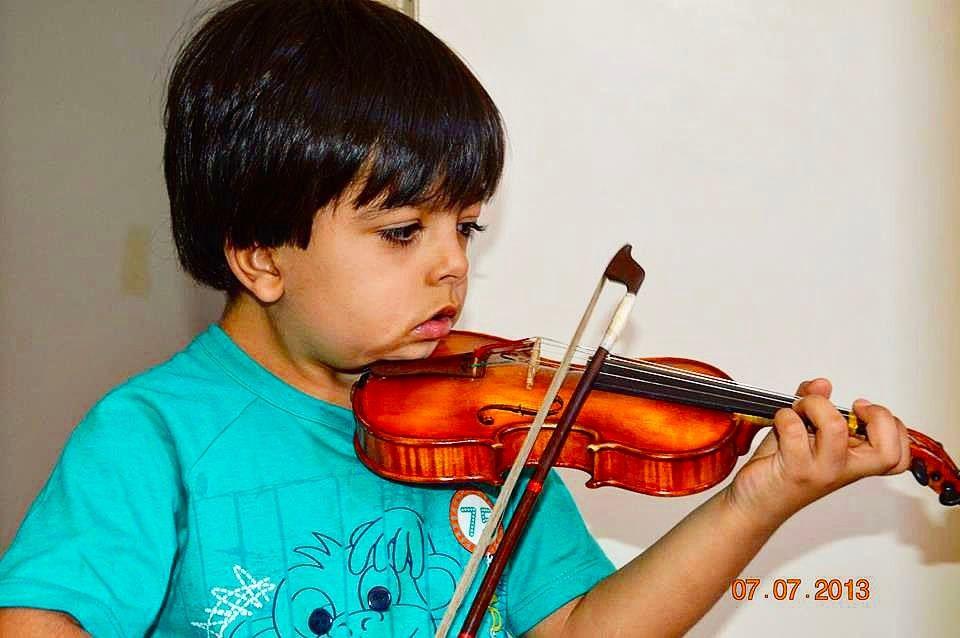 Um verdadeiro artista é uma pessoa que reúne em si sentimentos pensamentos e ações belas e esmeradas - Shinichi Suzuki  #PraCegoVer menino de 3 anos tocando violino com violino 1/16.