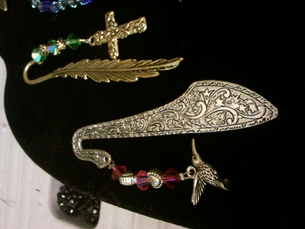 these are two book marks made with swarovski crystals, gold cross with green beads and hummingbird with purple crystals