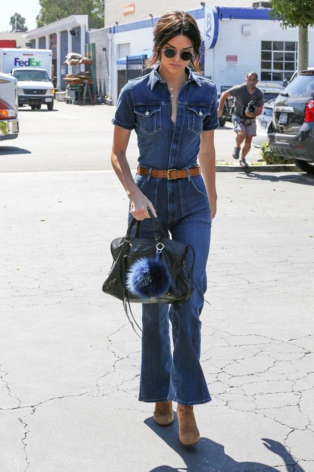 Kendall Jenner pairs a denim belted jumpsuit with a Balenciaga bag and suede ankle booties