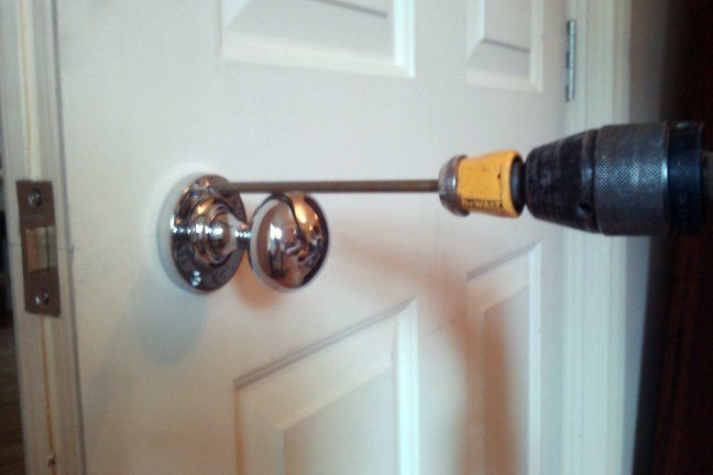 Use a long screwdriver bit or screwdriver to screw a door knob on ...
