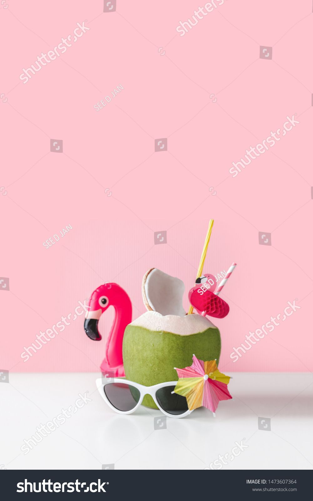Fresh coconut on a pastel pink background with flamingo inflatable drink holder and sunglasses summer vibes concept with copy space