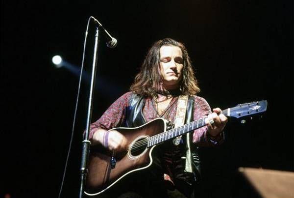 U2's Bono playing acoustic guitar on stage, 1987   BONO / U2