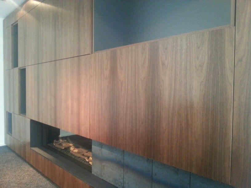 Vakkenkast Amerikaans notenhout. Openhaard metaal ruw afgewerkt. Kleine terug vallende deurtjes van ruw metaalplaat. TV paneellift ingewerkt.