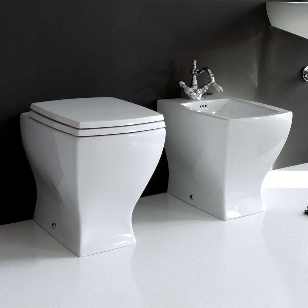 En el cuarto de baño hay el váter y el bidé de color ...