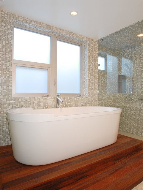 the master bath has a duravit tub on a stand made of plantation