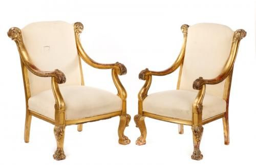 Italian, late 19th/early 20th century. A matched pair of Baroque style giltwood carved open armchairs each having a slightly arching neutral upholstered back w