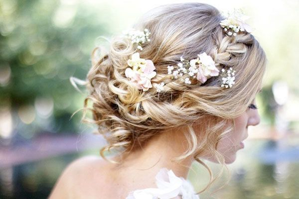 Cue the romance! Adding little flowers throughout your curly hairstyle that match your bouquet will give you a unique and cohesive look to your bridal style.