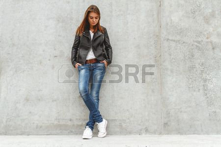 Portrait of a beautiful girl in jeans and a black leather jacket from the concrete wall