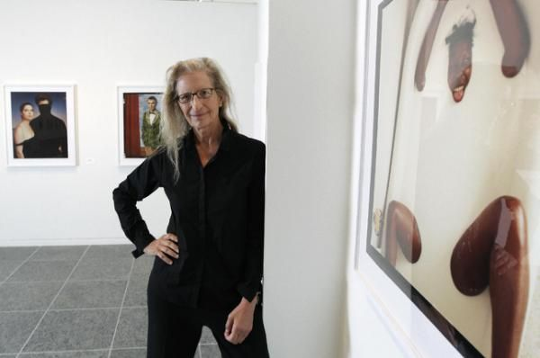 """Annie Leibovitz stands near some of her work before the opening of her exhibition at the Wexner Center for the Arts Friday, Sept. 21, 2012, in Columbus, Ohio. Leibovitz's exhibition features work from her """"Master Set,"""" an authoritative edition of 156 images. (AP Photo/Jay LaPrete) 