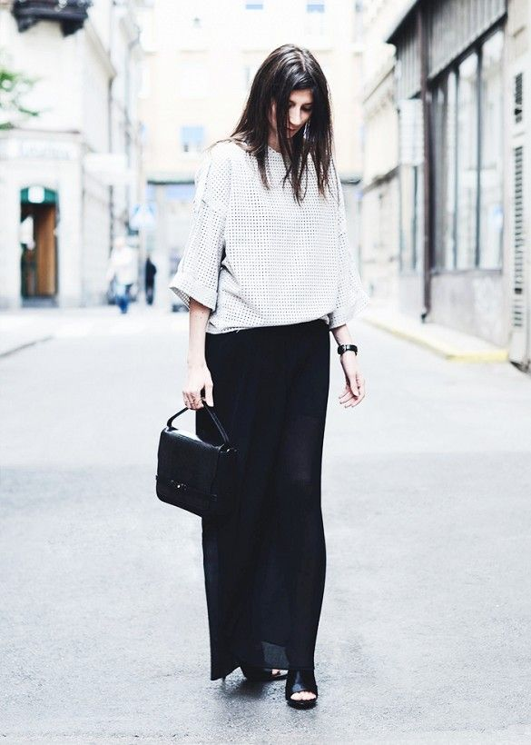 A black maxi skirt is worn with a boxy top, black mules and a top handle bag.