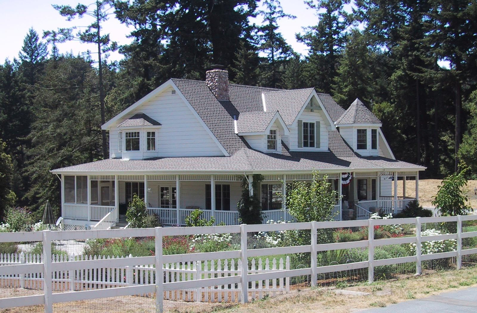 i love wrap around porches love the garden and pine trees if the