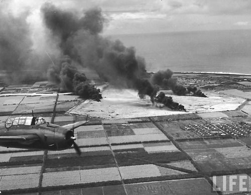 A Grumman TBF-1 Avenger flies over fields bombed by U.S. soldiers on the Japanese-occupied island of Saipan on June 30, 1944