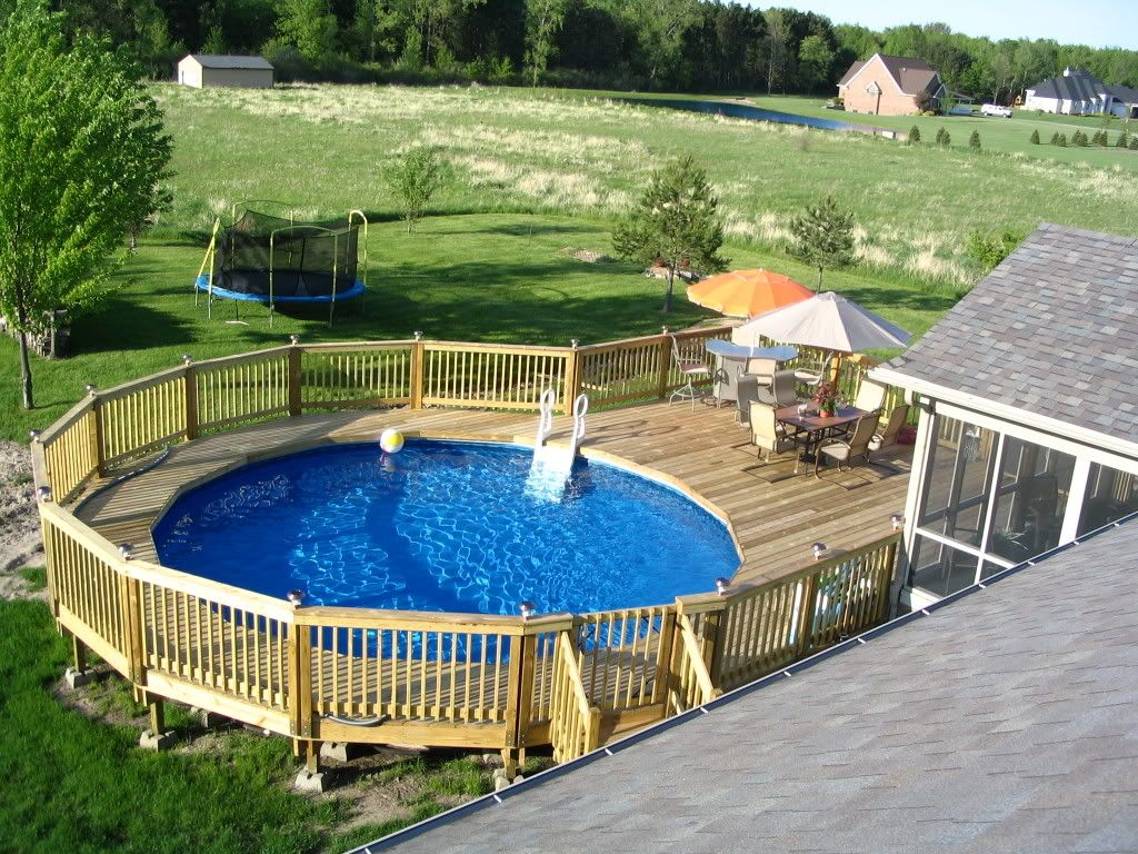 swiming pools hand rails with in ground ladders also above ground pool and wooden fence besides outdoor umbrellas wooden patio chairs ball beach deck