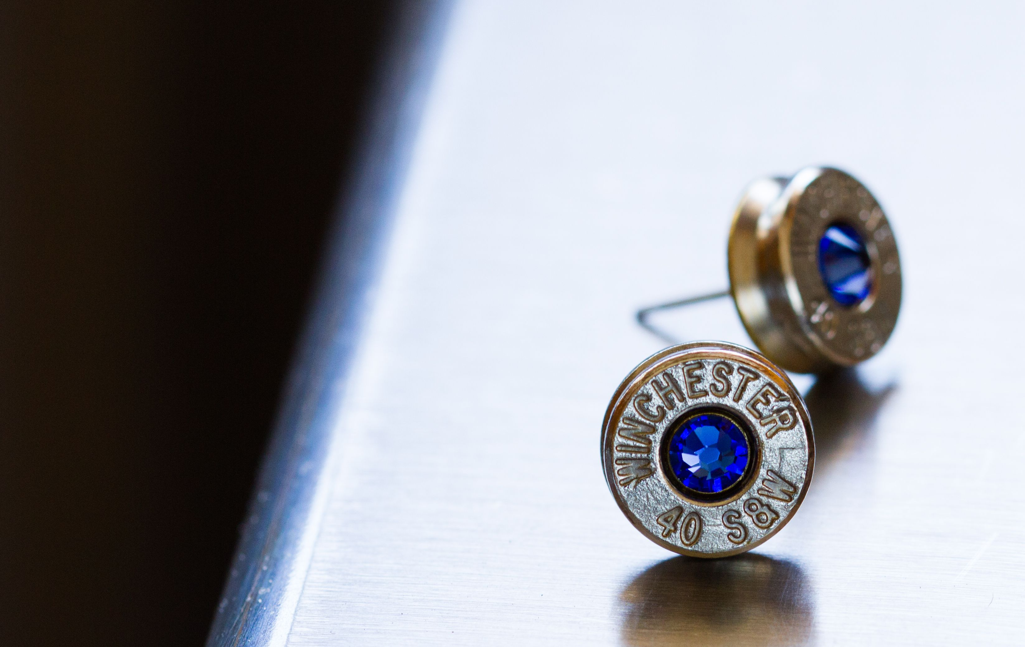 Nickel plated 40 cal with blue sapphire swarovski crystal.