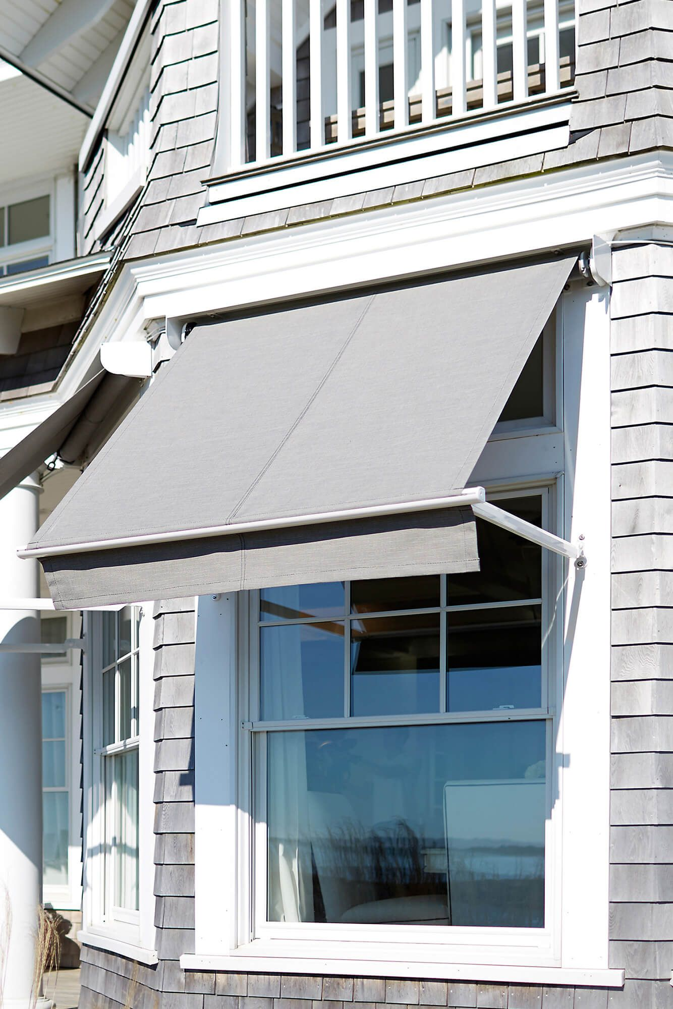 Home With Multiple Grey Window Awnings