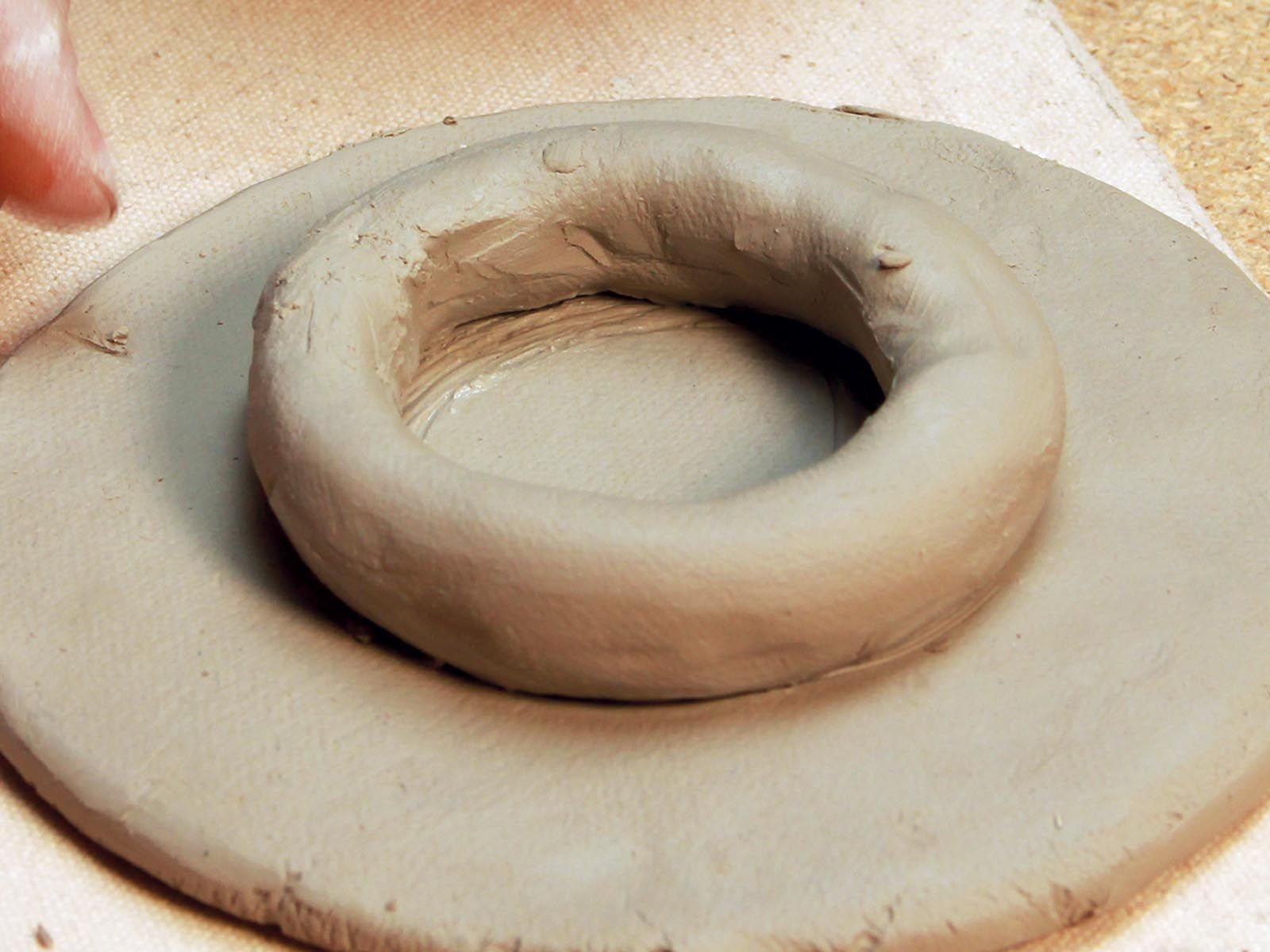 Alternately create the saucer foot with a coil of clay
